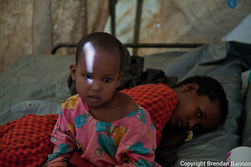 The daughter of Sharifa Iman Sugow, a Somali refugee resting at the MSF hospital while their youngest sibling is treated for malnutrition . They traveled by foot from Somalia to Dadaab refugee camp after their father died in Somalia.