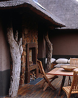 An outdoor fireplace has been built on the terrace under the eaves of the thatched roof of one of the lodge's guest suites