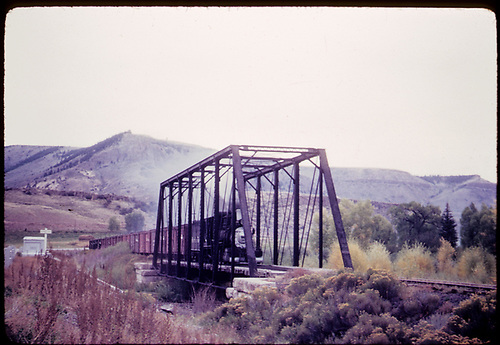 Train with box cars and stock cars crossing steel truss bridge possibly in Gunnison area.<br /> D&amp;RGW  Gunnison area ?, CO