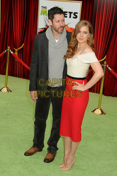"Darren Le Gallo & Amy Adams.""The Muppets"" Los Angeles Premiere held at the El Capitan Theatre, Hollywood, California, USA..November 12th, 2011.full length white top red skirt hand on hip off the shoulder nude shoes black jacket trousers grey gray top couple beard facial hair .CAP/ADM/BP.©Byron Purvis/AdMedia/Capital Pictures."