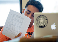 """Fernando Zepeda '14 works on his project, """"A Police Officers' Presentation of Self: The Social Power of the Uniform"""" as part of Occidental College's Summer Research Program, summer 2013. (Photo by Marc Campos, Occidental College Photographer)"""