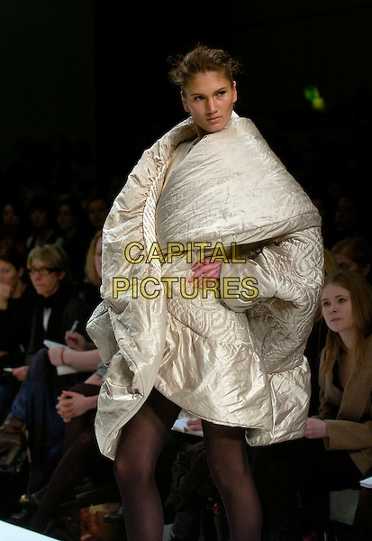 MODEL.At the Basso & Brooke a/w 2007/8 Catwalk Show during London Fashion Week, BFC Tent, London, England, February 15th 2007..half length runway modelling voluminous gold cream coat jacket puffy fat.CAP/CAN.©Can Nguyen/Capital Pictures