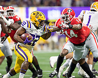 ATLANTA, GA - DECEMBER 7: Clyde Edwards-Helaire #22 of the LSU Tigers runs with the ball and is defended by DJ Daniel #14 of the Georgia Bulldogs during a game between Georgia Bulldogs and LSU Tigers at Mercedes Benz Stadium on December 7, 2019 in Atlanta, Georgia.