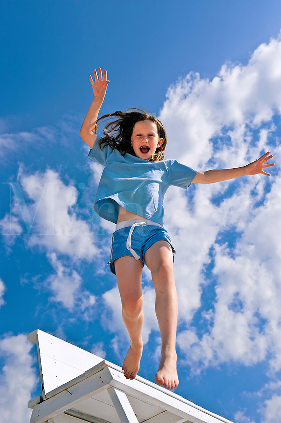 Girl jumping from a beach chair.