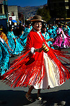 Dancing Cholita, dressed in the traditional indigenous Aymaran clothing of bowler hat and manta or shawl and pollera dress, celebrates a religious festival through the streets of La Paz, Bolivia.