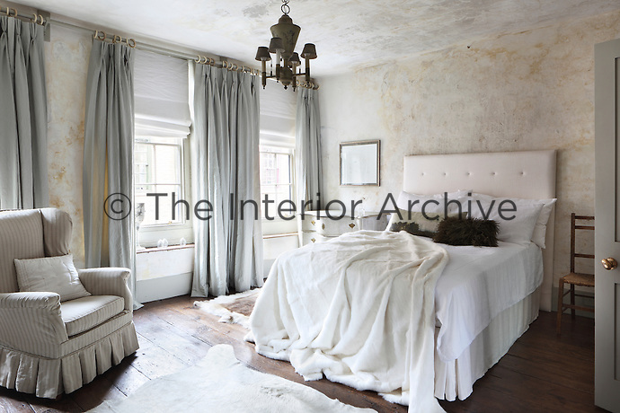 A bed with a white upholstered headboard in a period bedroom. The room is furnished with floor to ceiling curtains and the walls and ceiling have a distressed finish effect.