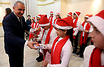 Palestinian Prime Minister Mohammad Ishtayeh, hands out gifts to children during a dinner hosted by the Ramallah Church Council, in the West Bank city of Ramallah, on December 30, 2019. Photo by Prime Minister Office