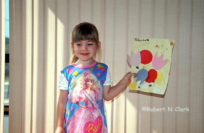 Girl showing off her preschool homework and artwork