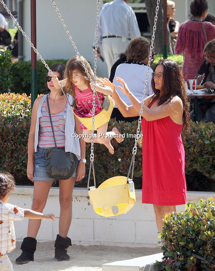 .June 27th 2010  Sunday  Exclusive ..Tia Carrere pushing her daughter Bianca on the swings at the park in Malibu. Bianca got her face painted red dress gold purse. ..Abilityfilms@yahoo.com.805-427-3519.www.AbilityFilms.com