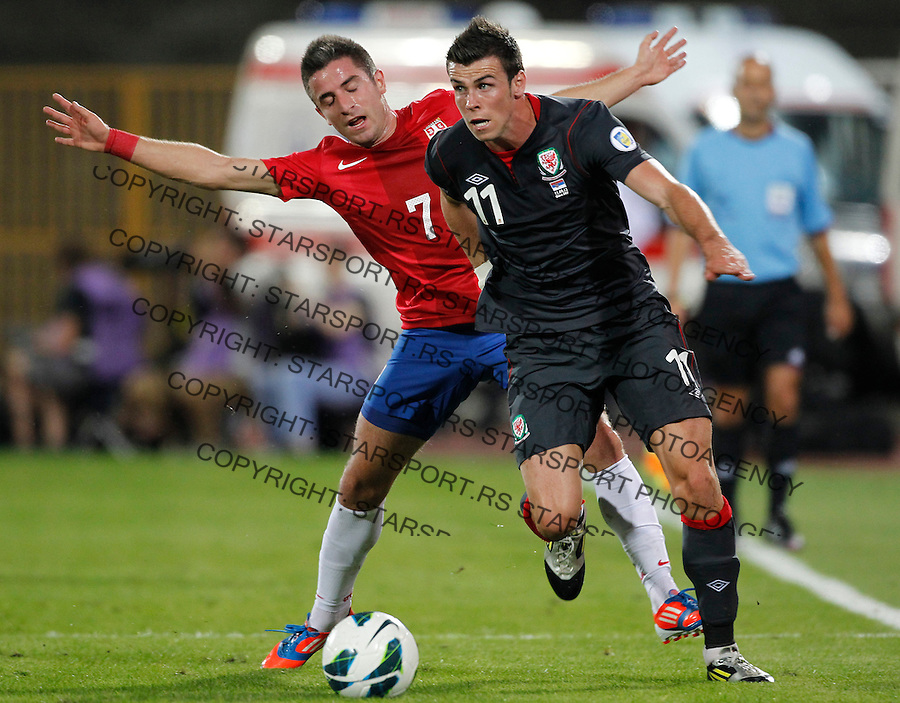 NOVI SAD, SERBIA - SEPTEMBER 11: Gareth Bale (R) of Wales is challenged by Zoran Tosic (L) of Serbia during the FIFA 2014 World Cup Qualifier at stadium Karadjordje Park between Serbia and Wales on September 11, 2012 in Novi Sad, Serbia (Photo by Srdjan Stevanovic/Getty Images)
