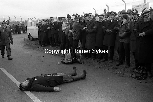 "For much of the 1980s, ""women's peace camps"" were established in protest at the deployment of cruise missiles. They came to be known as ""The Greenham Women"" or ""peace women"", and their 19-year protest drew worldwide media and public attention, often due to the peace women cutting through the fences of the base. A lone protestor makes a stand by breaking through the police cordon and peacefully prostrated herself in the middle of the road. She was very quickly removed. 1983"