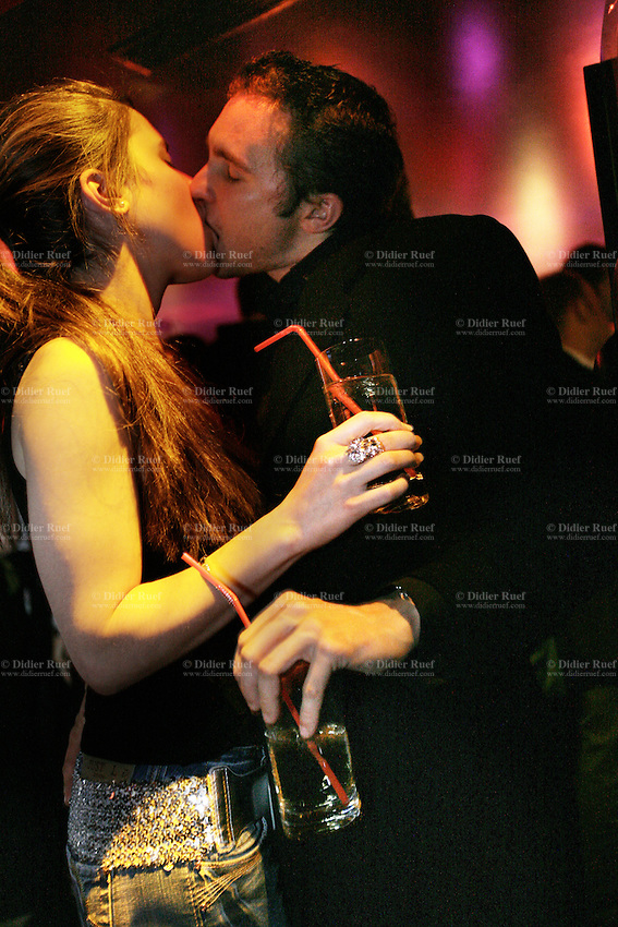 Switzerland. Canton Vaud. Lausanne. Red club. Exclusive and VIP party for the lauch of Xellent Vodka, the first and only Swiss Vodka. A couple is kissing on the mouth and having a drink on the dance floor. Night life. © 2006 Didier Ruef