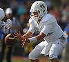 Oceanside quarterback No. 18 Vincent Guarino takes a snap during a Nassau County Conference I varsity football game against host East Meadow High School on Saturday, September 26, 2015. Oceanside won by a score of 14-7.<br /> <br /> James Escher