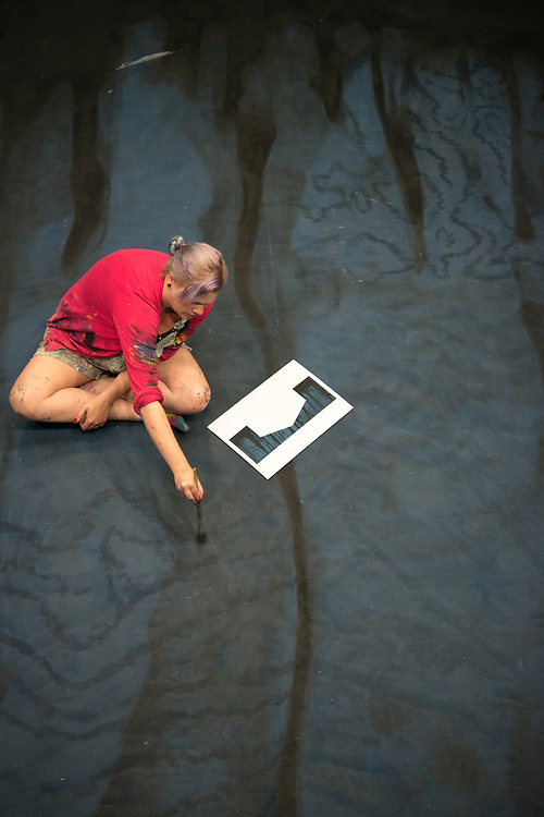 "Cassandra Leitz paints a scrim for the set of, ""Caroline,  or change"" for Tantrum Theater. Photo by Ben Siegel"