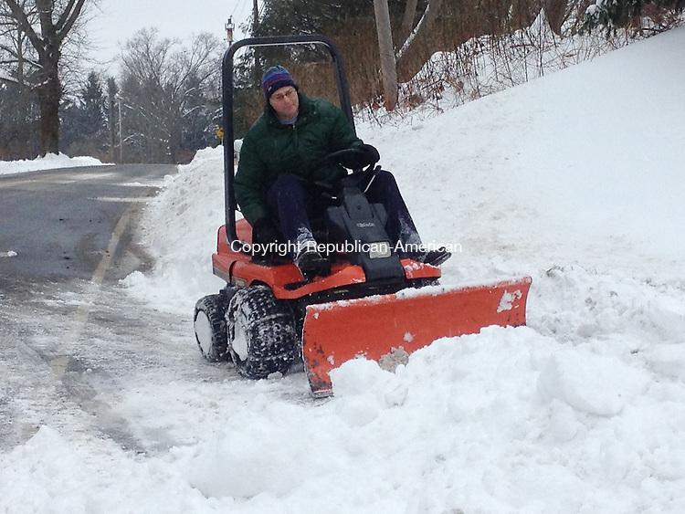 ROXBURY, CT -- Dennis Adilerti of Roxbury plows his driveway as the rain begins to fall on Rt. 67 Wednesday afternoon. Darlene Douty Republican-American