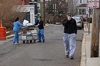 Medical workers wearing facemasks transport equipment back to the hospital as a patient (right) walks toward the Emergency Department as COVID-19 drive-through testing takes place in a parking lot near the Cambridge Health Alliance Women's Health Hospital in Somerville, Massachusetts, on Mon., March 23, 2020. Patients could make appointments to drive through the parking lot to get tested for the virus during the ongoing Coronavirus (COVID-19) global pandemic. This location is one of a handful of such testing facilities that have opened in the Boston area in the past week.