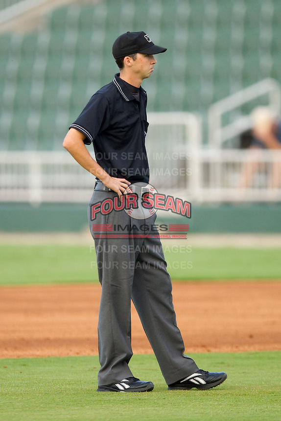 Umpire Thomas Newsom handles the calls on the bases during a South Atlantic League game between the Greensboro Grasshoppers and the Kannapolis Intimidators at Fieldcrest Cannon Stadium August 2, 2010, in Kannapolis, North Carolina.  Photo by Brian Westerholt / Four Seam Images
