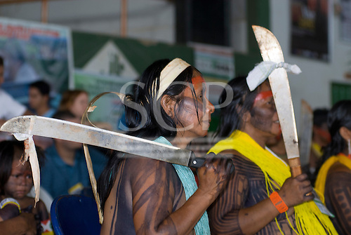 "Altamira, Brazil. ""Xingu Vivo Para Sempre"" protest meeting about the proposed Belo Monte hydroeletric dam and other dams on the Xingu river and its tributaries. Two Kayapo women with machetes and a piece of the electricity company representative's shirt tied to it."