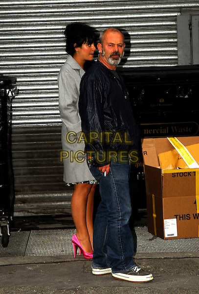 """LILY ALLEN & KEITH ALLEN.Sneak out for a cigarette at the launch party of """"'Lily Loves"""" collection at New Look Oxford Street, London, England..May 8th, 2007.full length father dad daughter family grey gray coat jacket pink shoes heels jeans denim black.CAP/IA.©Ian Allis/Capital Pictures"""