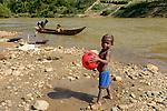 MADAGASCAR, region Manajary, town Vohilava, small scale gold mining, children panning for gold at river / MADAGASKAR Mananjary, Vohilava, kleingewerblicher Goldabbau, Kinder waschen Gold am Fluss, Junge mit Ball
