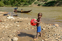 MADAGASCAR, region Manajary, town Vohilava, small scale gold mining, children panning for gold at river / MADAGASKAR Mananjary, Vohilava, kleingewerblicher Goldabbau, Kinder waschen Gold am Fluss, Junge mit Ball