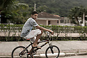 Kid riding his bike in the street of Guaruja in Brazil.