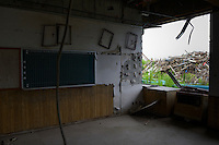 A derelict elementary school. The tsunami reached the ceiling of the ground floor. Namie, Fukushima Prefecture, Japan, August 2, 2013. The town of Namie was evacuated following the nuclear accident of March 2011. Residents can only return for short periods to tend to their former homes and pick up belongings, and are not permitted to stay overnight.