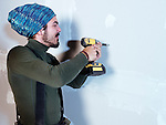 Portrait of a smiling young man contractor worker mounting drywall with a screw gun renovating interior