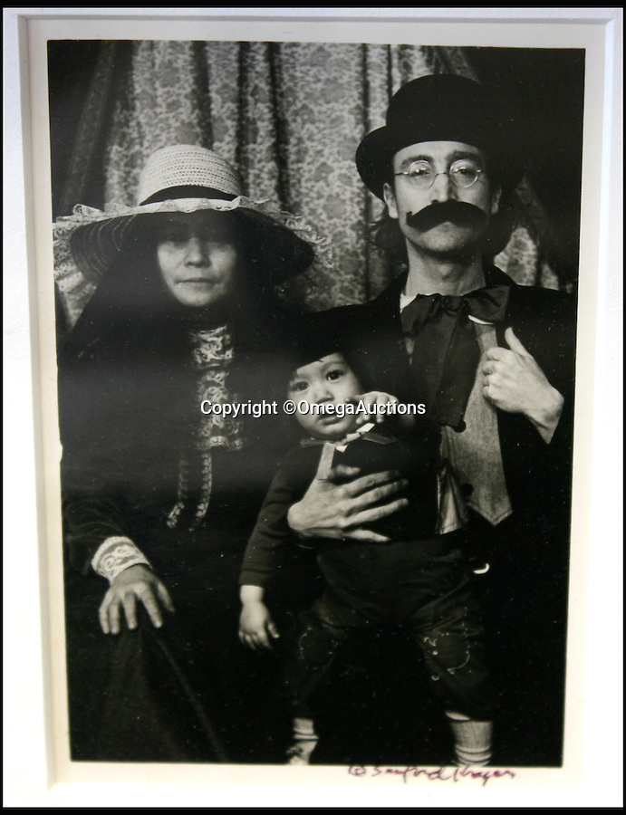 BNPS.co.uk (01202 558833)<br /> Pic: OmegaAuctions/BNPS<br /> <br /> Jonh Lennon with his wife Yoko Ono and son Sean.<br /> <br /> A remarkable set of family photos that show John Lennon larking around and dressing as a woman have emerged for sale.<br /> <br /> The five original black and white pictures offer a rare insight into the personal life of the mega star and show Lennon, his wife Yoko Ono and baby son Sean having fun in costume while on holiday in America. <br /> <br /> They were taken in a vintage clothing photography studio in Stockbridge, Massachusetts in 1977 - just three years before the music icon was shot outside his New York apartment - and also feature Sean's nanny and a friend.