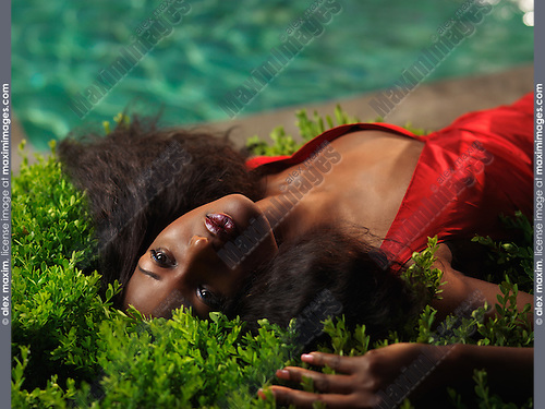 Young black woman in red dress lying on the bushes beside a pool