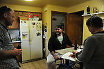 Cousin Garrick Leitelt, 38, and Mike Padgett, 30, have a beer in the kitchen of the home they share with extended family in Chicago Ridge, Illinois on April 21, 2015.  Padgett is a student at the University of Illinois Chicago doing an externship in the neuroscience imaging and microscopy lab and bar tends at the Drum and Monkey on campus for extra cash.