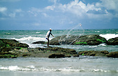 Sauipe, Brazil. Man fishing with a net from the rocks on the sea shore. Bahia State.