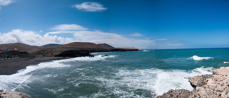 Panorama of the cliffs and beach at Puerto de la Pena (Ajui), Fuerteventura, Canary Islands, Spain. Due to its volcanic origins, a number of beaches in Fuerteventura have very dark, almost black, sand. The white sand on beaches on the east coast of the island comes from the Sahara desert, carried by the winds.