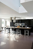 In the bright and spacious kitchen/living area a pared-down colour scheme of black, white and grey emphasises the sculptural aspect of the minimalist design