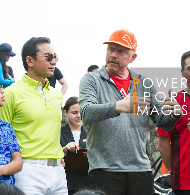 Tennis Legend Boris Becker (orange cap), and Mission Hills vice-chairman Tenniel Chu (yellow shirt) observe junior tennis players play at Mission Hills Resort on 19 March 2016, in Shenzhen, China. Photo by Lucas Schifres / Power Sport Images