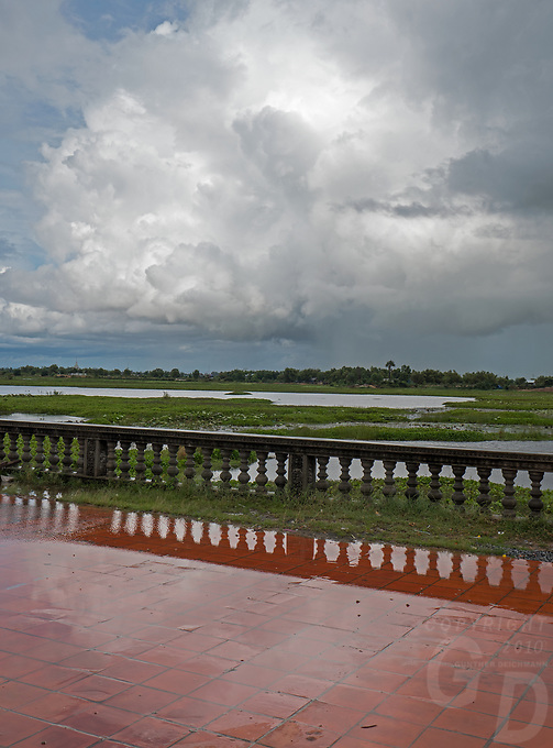Overlooking the vast rice fields from a Monastery during a heavy Monsoon rain shower near the Tonle Sap lake, Cambodia