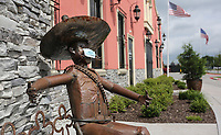 A metal sculpture sits with open arms and a mask Friday, June 26, 2020, outside the Azul Tequila Mexican Cuisine restaurant in Springdale. Restaurants and bars have recently opened in Arkansas following specific guidelines because of the covid-19 pandemic. Check out nwaonline.com/200627Daily/ and nwadg.com/photos for a photo gallery.<br /> (NWA Democrat-Gazette/David Gottschalk)