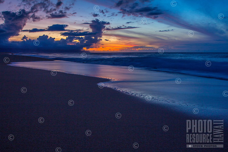 Evening glow reflects in the water along a North Shore shoreline on O'ahu.