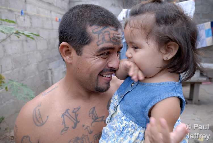 Henri Aguilar with his one-year old daughter Genesis in the yard of their home in Chamelecon, a poor neighborhood of San Pedro Sula, Honduras. This photo was captured May 2, 2007. On May 7, 2007, Aquilar was assassinated in his home by three masked men. A former member of the Mara Salvatrucha, a notorious street gang, Aguilar had left gang life behind, was married, working full time, and heavily involved in the local Catholic parish. Gangs have grown in recent years in Central America, and many young men get involved because they have few other options in the war-torn region. Once in a gang, however, it's very difficult to leave.