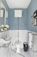An old fashioned bathroom with a wall mounted cistern, exposed metal pipes and metro style wall tiles