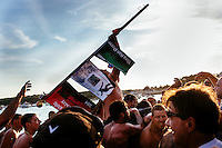The winner of the Greasy Pole Contest celebrates and carries the flag as he returns to shore during St. Peter's Fiesta in Gloucester, Massachusetts, USA. The contest has been held since 1931 and involves participants running along a greased horizontal pole over Gloucester Harbor.
