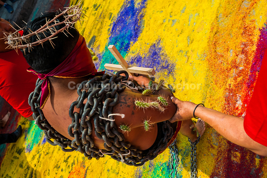 A chained penitent, wearing a crown of thorns and cactus spines stuck to his body, walks on a colorful sawdust carpet during the Holy week procession in Atlixco, Mexico, 30 March 2018. Every year on Good Friday, dozens of anonymous men of all ages voluntarily undergo pain and suffering during the religious procession of the 'Engrillados' (the Shackled ones) in Puebla state, central Mexico. Wearing heavy chains on their shoulders covered with prickling cacti while being burned by the hot midday sun, they recall Jesus Christ's death by crucifixion and demonstrate their religiosity and faith.