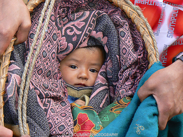 On a bus from Kathmandu to Dunche in northern Nepal a woman boarded with a covered basket carried by a strap across her forehead. A tightly swaddled and very relaxed  baby was revealed later on.