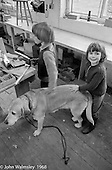 Stroking Neill's dog in the carpentry room, Summerhill school, Leiston, Suffolk, UK. 1968.