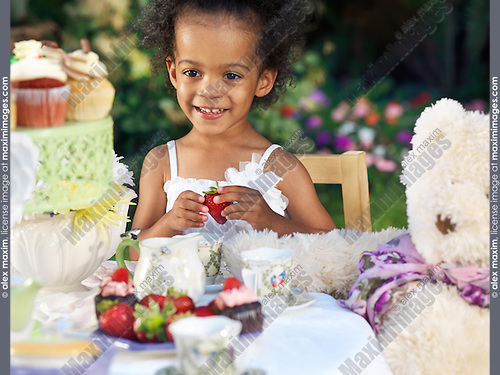 Happy smiling three year old girl having a party outdoors sitting at the table with fruits and cupcakes