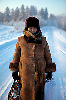 A portrait of a woman standing on a snow-covered street in the village of Oymyakon. She walks weekly to the village from her home seven kilometers away in the extreme cold to do her shopping. The village is known as the Northern Pole of Cold as it has recorded the lowest ever temperatures for an inhabited place on earth, the coldest being -67.7 degrees celcius.