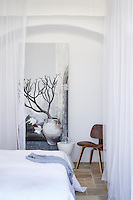A wood Eames chair is placed in the corner of a white bedroom where the bed is surrounded by a sheer curtain.