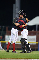 Batavia Muckdogs relief pitcher Josh Alberius (15) and catcher David Gauntt (7) embrace after closing out a game against the Lowell Spinners on July 12, 2017 at Dwyer Stadium in Batavia, New York.  Batavia defeated Lowell 7-2.  (Mike Janes/Four Seam Images)