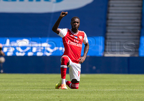 20th June 2020, American Express Stadium, Brighton, Sussex, England; Premier League football, Brighton versus Arsenal ;  Arsenals Nicolas Pepe takes a knee with teammates in support of the Black Lives Matter campaign prior to the match