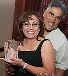 Virginia Bazan and husband Rudy Bazan pose with Virginia's Strategic Partner Award for Volunteer of the year.